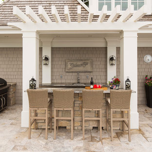 Large arts and crafts backyard stone patio kitchen photo in Minneapolis with a pergola