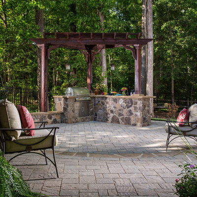 Inspiration for a mid-sized timeless backyard concrete paver patio kitchen remodel in Charlotte with a pergola