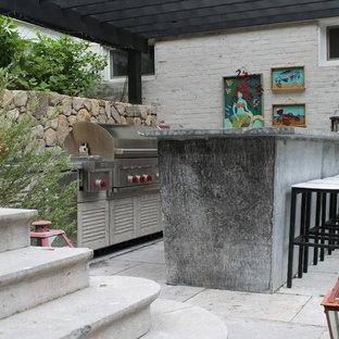 Immagine di un grande patio o portico eclettico dietro casa con pavimentazioni in cemento e una pergola