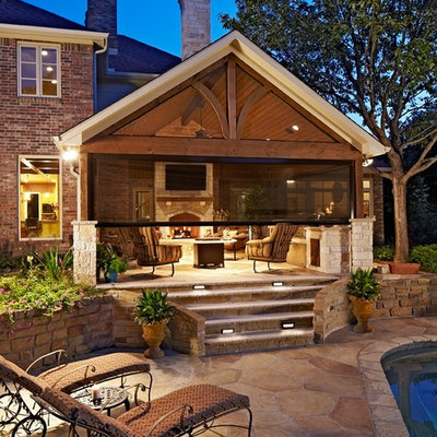Large elegant backyard stone patio kitchen photo in Dallas with a roof extension