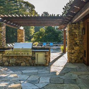 Inspiration för mycket stora rustika uteplatser på baksidan av huset, med utekök, naturstensplattor och en pergola