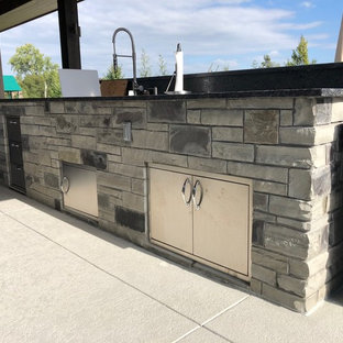 Immagine di un patio o portico minimalista dietro casa con cemento stampato e un tetto a sbalzo
