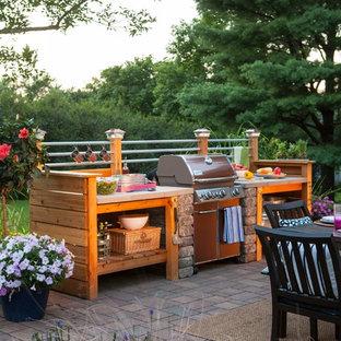 Idées déco pour une petite terrasse avec une cuisine extérieure arrière industrielle avec des pavés en brique.