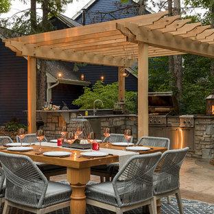 Immagine di un patio o portico tradizionale di medie dimensioni e dietro casa con pavimentazioni in pietra naturale e una pergola