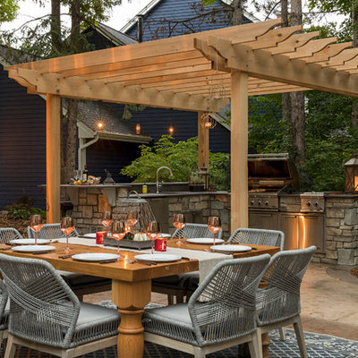 Inspiration for a mid-sized timeless backyard stone patio kitchen remodel in Minneapolis with a pergola