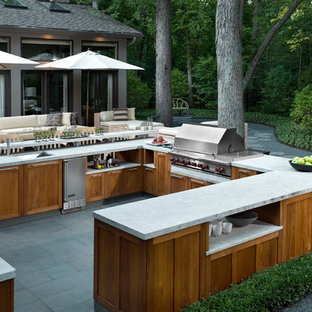 Photo of a large contemporary backyard patio in Chicago with an outdoor kitchen, tile and no cover.