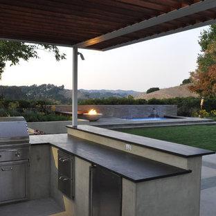 Inspiration pour une terrasse design avec un foyer extérieur et une pergola.