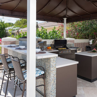 This is an example of a small world-inspired back patio in Miami with an outdoor kitchen, an awning and brick paving.