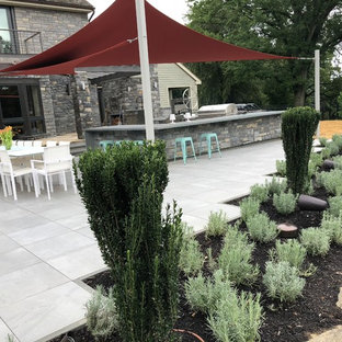 This is an example of a large contemporary back patio in Philadelphia with an outdoor kitchen, tiled flooring and an awning.