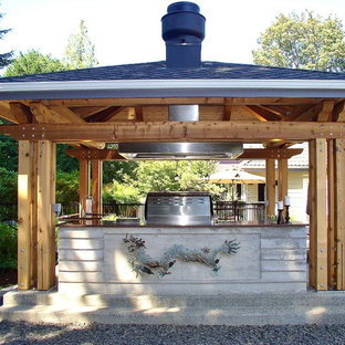 Inspiration for a zen backyard concrete patio kitchen remodel in Seattle with a pergola