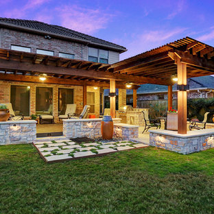 Design ideas for a large traditional back patio in Houston with an outdoor kitchen, natural stone paving and a pergola.