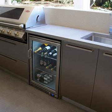 Outdoor Kitchen with a polished concrete benchtop & stainless steel doors.