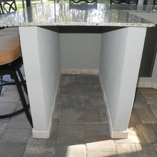 Inspiration for a large traditional back patio in Jacksonville with an outdoor kitchen, natural stone paving and an awning.