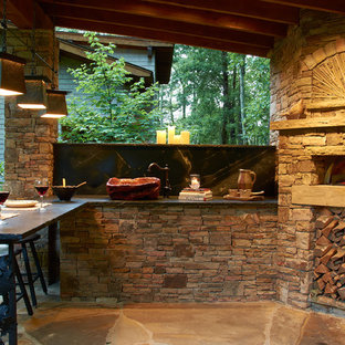 Inspiration for a mid-sized rustic backyard stone patio kitchen remodel in Other with a gazebo