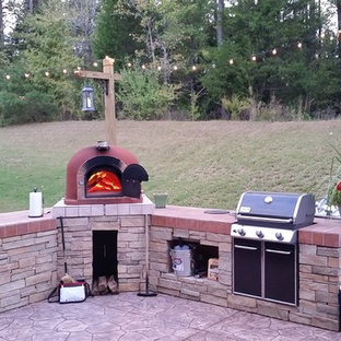 Patio kitchen - small rustic backyard stone patio kitchen idea in New York with no cover