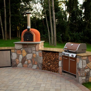 Inspiration for a mid-sized timeless backyard brick patio kitchen remodel in New York with a roof extension