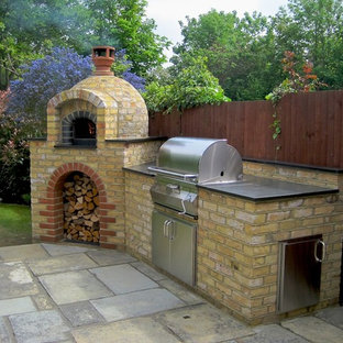 Photo of a medium sized traditional back patio in Kent with an outdoor kitchen, brick paving and no cover.