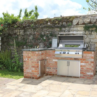 Small classic courtyard patio in Kent with an outdoor kitchen, brick paving and no cover.