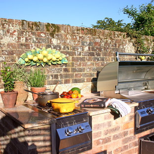Photo of a small classic courtyard patio in Kent with an outdoor kitchen, brick paving and no cover.