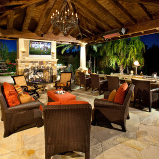 Example of an island style patio design in Orange County with a fire pit