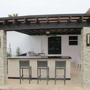 Patio kitchen - huge modern backyard stone patio kitchen idea in Miami with a pergola