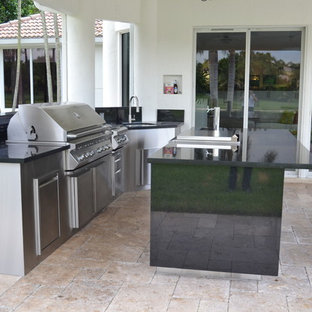 Design ideas for an expansive modern back patio in Miami with an outdoor kitchen, natural stone paving and a roof extension.