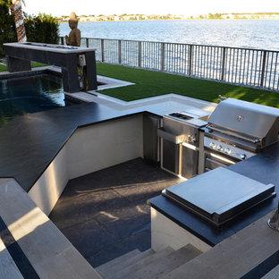 Patio kitchen - huge modern backyard stone patio kitchen idea in Miami