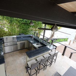 Example of a huge minimalist backyard stone patio kitchen design in Miami with a pergola