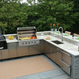 Example of a large classic backyard concrete paver patio kitchen design in New York with an awning