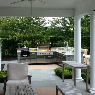 Large elegant backyard concrete paver patio kitchen photo in New York with an awning