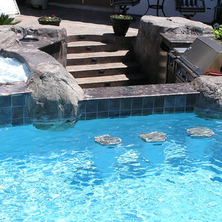 Example of a large backyard stone patio kitchen design in Las Vegas with no cover
