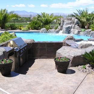 Large backyard stone patio kitchen photo in Las Vegas with no cover
