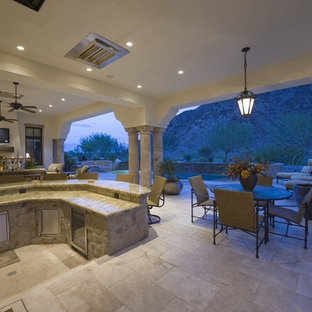 Example of a large backyard tile patio kitchen design in Las Vegas with a roof extension