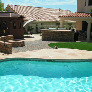 Patio kitchen - large backyard stone patio kitchen idea in Las Vegas with no cover