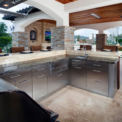 Example of a huge mountain style backyard stone patio design in Orange County with a roof extension