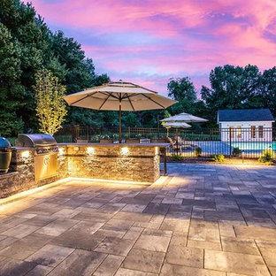 Cette photo montre une terrasse avec une cuisine extérieure arrière moderne avec des pavés en pierre naturelle et un auvent.