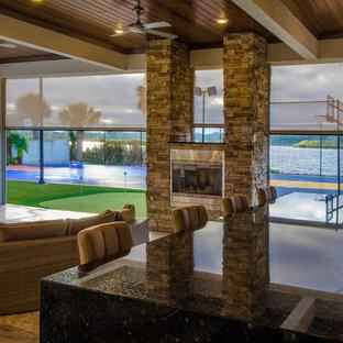 Foto di un ampio patio o portico design dietro casa con pavimentazioni in pietra naturale e un tetto a sbalzo