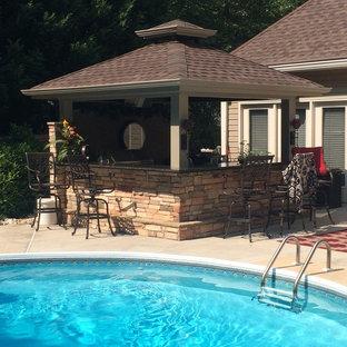 Esempio di un grande patio o portico tradizionale dietro casa con lastre di cemento e un gazebo o capanno