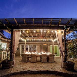 Exemple d'une grande terrasse arrière nature avec une pergola.