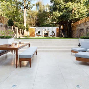 Huge transitional backyard tile patio photo in London with no cover