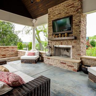 Foto di un grande patio o portico classico dietro casa con lastre di cemento, un tetto a sbalzo e un caminetto