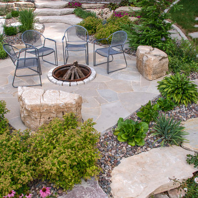 Mountain style backyard stone patio photo in Milwaukee with a fire pit and no cover