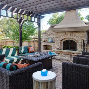 Idee per un grande patio o portico minimal dietro casa con pavimentazioni in cemento, una pergola e un caminetto