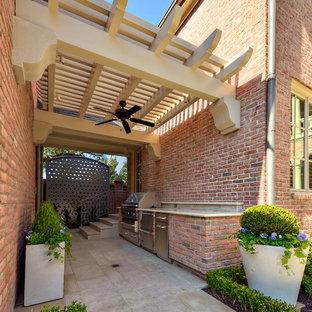 Patio kitchen - eclectic patio kitchen idea in Dallas with a pergola