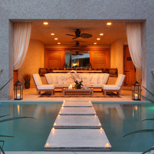 Example of a large trendy backyard concrete paver patio fountain design in Miami with a roof extension