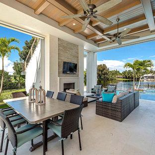 Immagine di un patio o portico stile marino dietro casa con piastrelle, un tetto a sbalzo e un caminetto