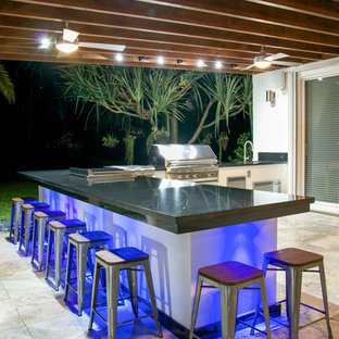 Design ideas for a large contemporary back patio in Miami with an outdoor kitchen, natural stone paving and an awning.