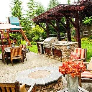 Esempio di un patio o portico chic di medie dimensioni e dietro casa con un focolare, graniglia di granito e nessuna copertura
