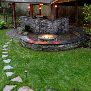 Inspiration for a large timeless backyard stone patio kitchen remodel in Seattle with a gazebo