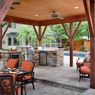 Aménagement d'une grande terrasse avec une cuisine extérieure arrière classique avec des pavés en brique et un gazebo ou pavillon.